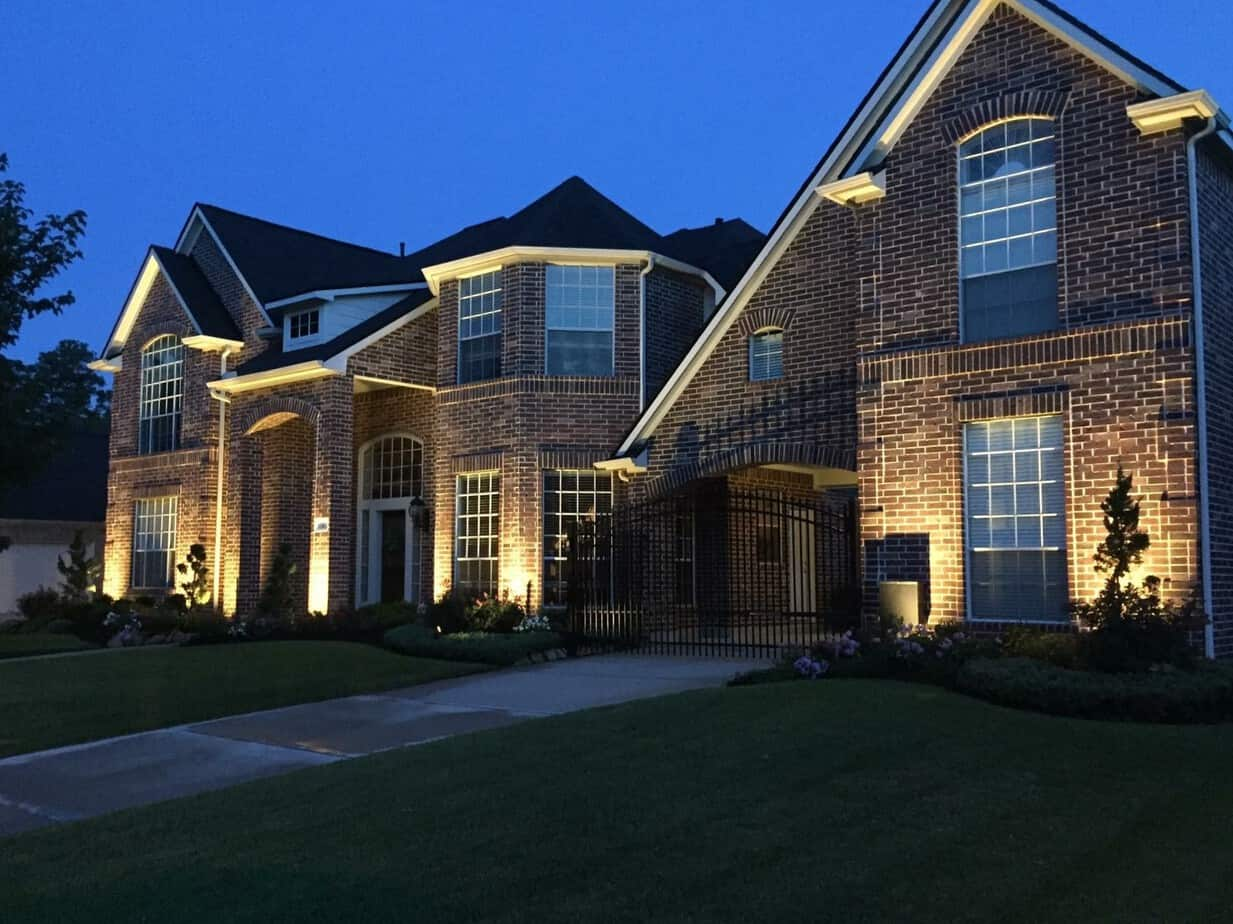A beautiful home in Huffman Texas features outdoor uplighting