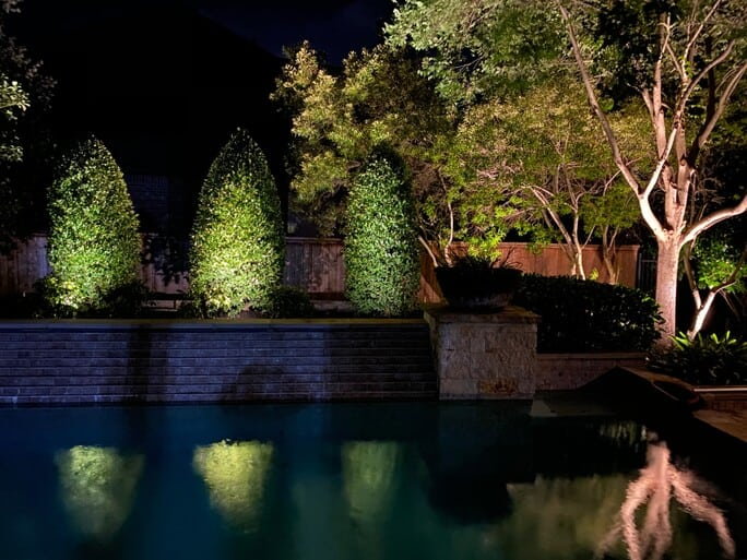 Lighting techniques like shadowing are used to brighten 3 shrubs against a wall, with a lake reflecting the highlighted plants.