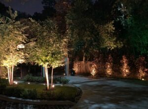 This driveway with ground lights lit up along both sides of the pavement is a recommended spot for where to place landscape lighting
