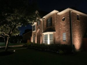 A brick house lit up  at night with uplighting, one of the many different types of landscape lighting
