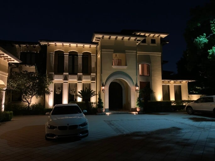 The memorial villages tx villa lit up at night with 2 cars on the left and right side of the driveway