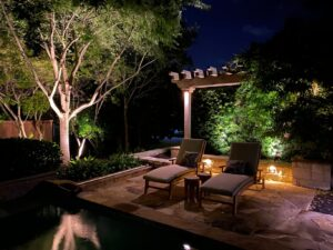 Patio lighting highlights two pool chairs under a small wooden awning