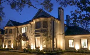 The West University Place Texas Hearth Home has big windows and a door arch that are lit up at dusk