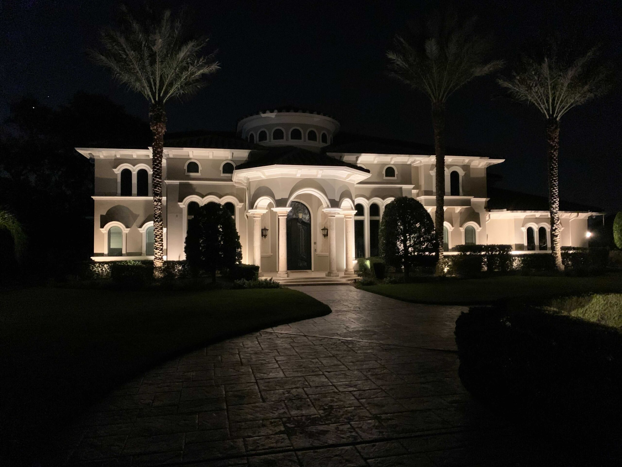The Woodlands Houston Home lit up at night with columns over an arched front door and 3 palm trees in front
