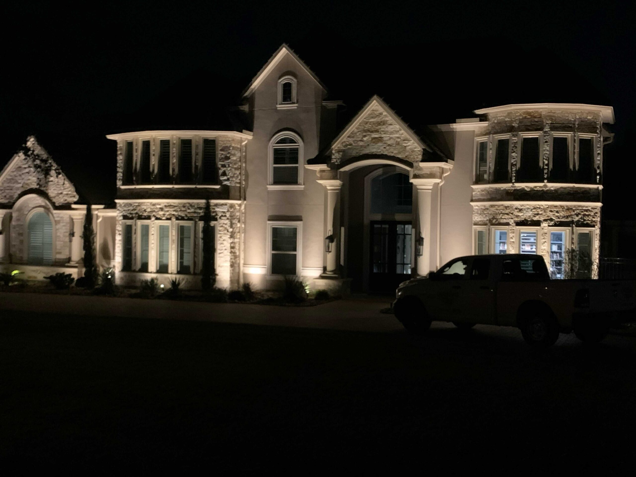 The front of the Woodlands Houston Home lit up at night with a truck parked in front