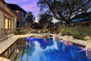 A beautiful pool sits under trees, creating an outdoor haven