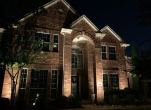 Uplighting on a 2 story brick house at night with a tree in front