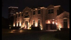 The tanglewood houston manor is a large brick two story house with a fenced in garage