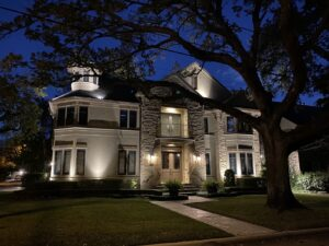 The 3 story Bellaire Tx abode sits lit up at night with a large tree to the right of the walkway