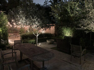 The backyard of a memorial villages houston home with a patio table and chairs and string lights