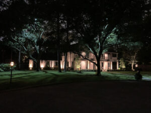 A two story brick memorial villages houston home sits on a large lot surrounded by trees