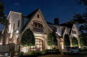 A two story stone detailed house with a Juliette balcony in Tanglewood Houston