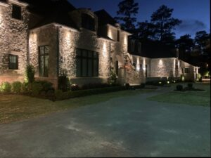 A stone two story house with a large driveway in front is lit up at night with downlighting