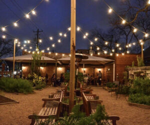 Business maintenance lighting maintains the outdoor seating area at a restauruant with wooden tables, benches, and string lights